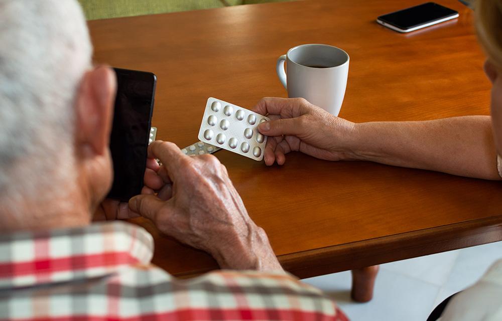 Casal fazendo compras a distância no aplicativo da farmácia - 60 mais